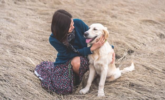 Glimlachende vrouw met schattige hond op de natuur van de vroege lente