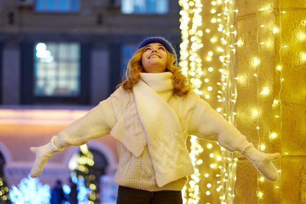 Glimlachende vrouw met slingers en vakantielichten op feestelijke kerstmis of nieuwjaarmarkt. dame draagt klassieke stijlvolle winter gebreide trui en wanten