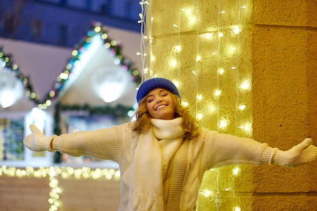 Glimlachende vrouw met slingers en vakantielichten op feestelijke kerstmis of nieuwjaarmarkt.