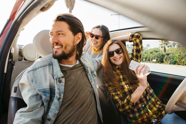 Glimlachende vrouw met smartphone en positieve man in auto dichtbij dame die uit van auto leunt