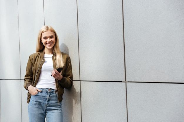 Glimlachende vrouw met smartphone het kijken