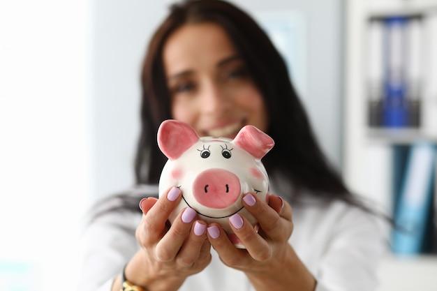 Glimlachende vrouw met spaarvarken
