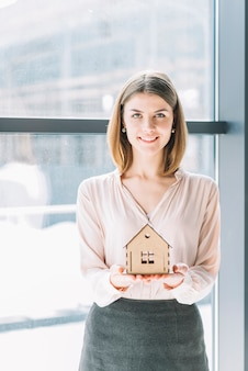 Glimlachende vrouw met stuk speelgoed huis