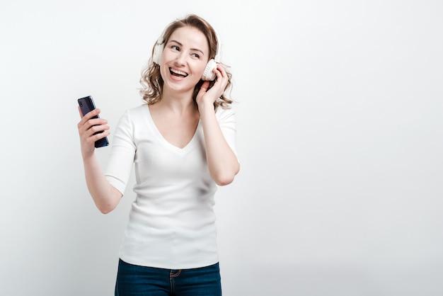 Glimlachende vrouw met telefoon in hoofdtelefoons het dansen. geïsoleerd