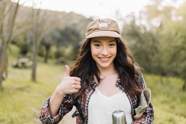 Glimlachende vrouw met thermosflessen die duim-omhoog gesturing