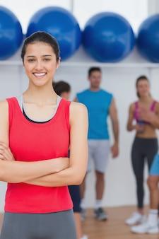 Glimlachende vrouw met vrienden op achtergrond bij geschiktheidsstudio