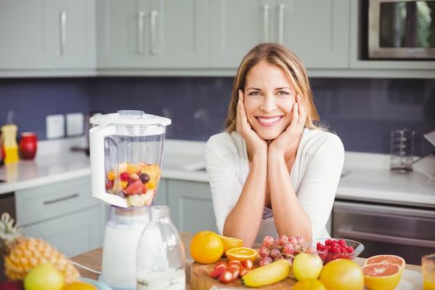Glimlachende vrouw met vruchten in een keuken