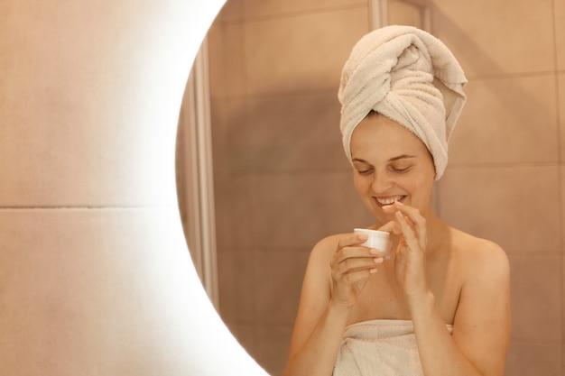 Glimlachende vrouw met witte handdoek op haar hoofd die crème in handen houdt voordat ze zich aanbrengt, met blote schouders staat en positieve emoties uitdrukt.