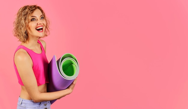 Glimlachende vrouw met yogamat. thuis sporten. gezonde levensstijl. gelukkig meisje met fitnessmat. kopieer ruimte voor reclame.