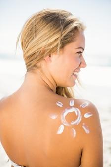 Glimlachende vrouw met zonnebrandcrème op haar huid