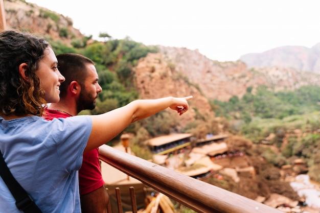 Glimlachende vrouw naast een man die aan de horizon voor een dor landschap met kleine huizen richt. ouzoud-watervallen in marokko
