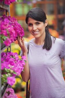 Glimlachende vrouw ongeveer om bloemen te ruiken