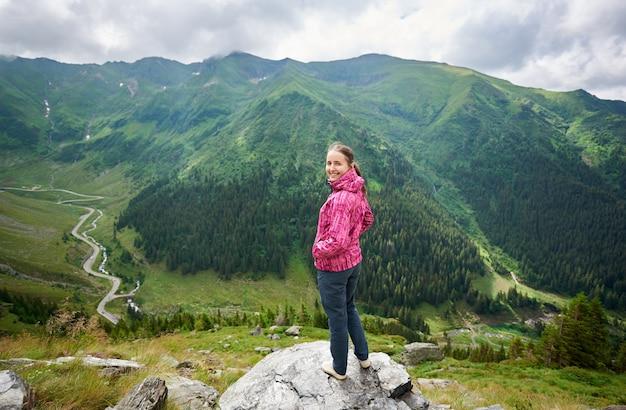Glimlachende vrouw op de rots in de bergen en de bossen van het aardlandschap