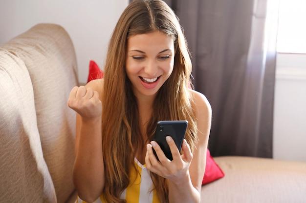 Glimlachende vrouw op een bank die een smartphone met behulp van