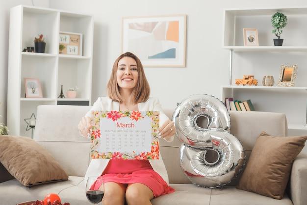 Glimlachende vrouw op gelukkige vrouwendag die een kalender uithoudt die op de bank in de woonkamer zit