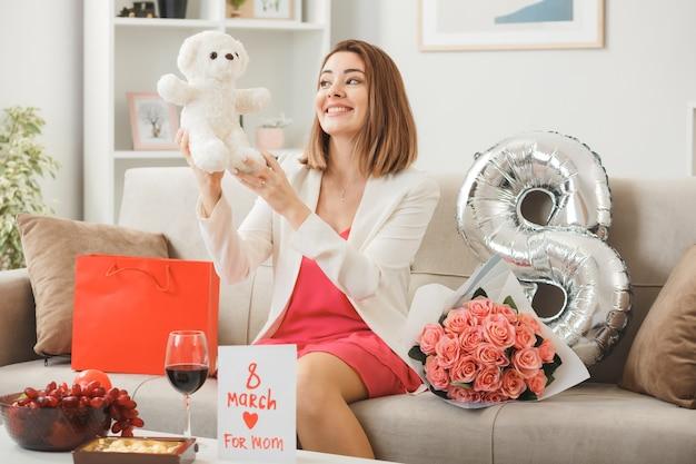 Glimlachende vrouw op gelukkige vrouwendag die teddybeer vasthoudt en bekijkt die op de bank in de woonkamer zit