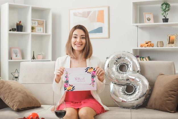 Glimlachende vrouw op gelukkige vrouwendag met wenskaart zittend op de bank in de woonkamer