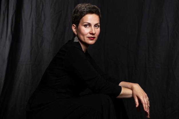Glimlachende vrouw op middelbare leeftijd met een kort kapsel. portret op een zwarte achtergrond.