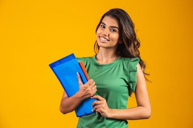 Glimlachende vrouw student met schoolboeken in handen op gele achtergrond.