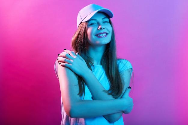 Glimlachende vrouw tegen roze neonmuur die omhelzen