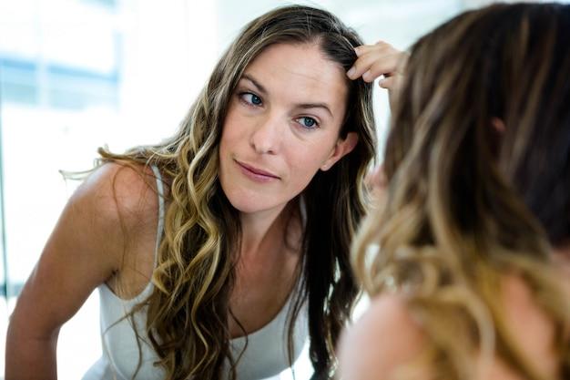 Glimlachende vrouw tot vaststelling van haar haren in de badkamerspiegel