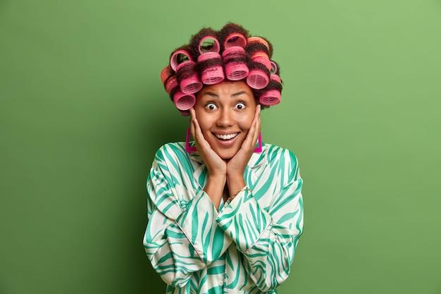 Glimlachende vrouw van gemengd ras die aangenaam verrast is, houdt de handen op de wangen, verbaasd over geweldig nieuws, draagt haarkrulspelden en kamerjas, geïsoleerd op groene muur