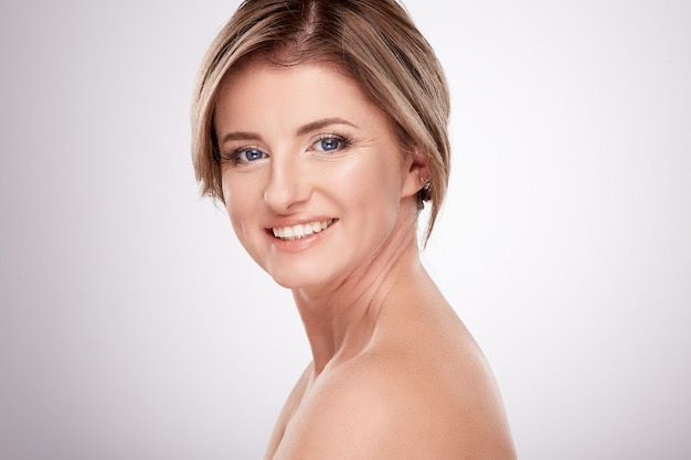 Glimlachende vrouw van gemiddelde leeftijd met naaktmake-up en naakte schouders poseren muur, schoonheid foto concept, huid en rimpels behandeling