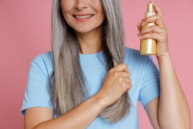 Glimlachende vrouw van middelbare leeftijd brengt sprayproduct aan op grijze haarlok die op een roze achtergrond staat in studioclose-up. volwassen schoonheid levensstijl