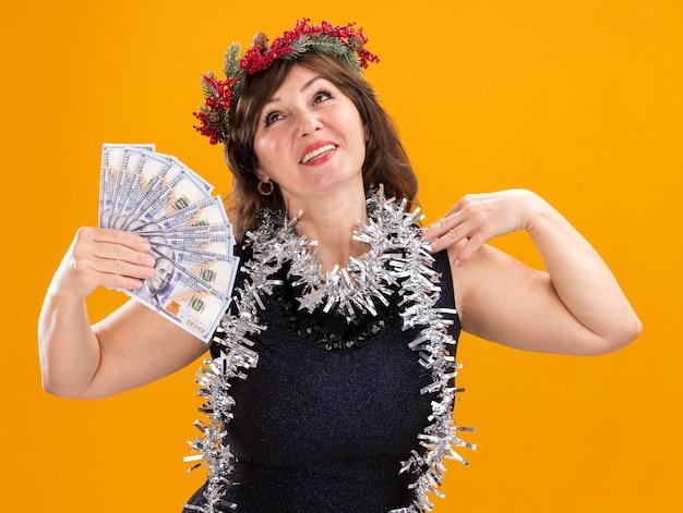 Glimlachende vrouw van middelbare leeftijd die kerstmis hoofdkroon en klatergoudslinger dragen rond hals die geld aanraken schouder opzoeken geïsoleerd op oranje achtergrond