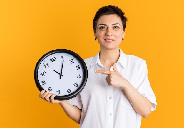 Glimlachende vrouw van middelbare leeftijd die naar de klok wijst en naar de camera kijkt