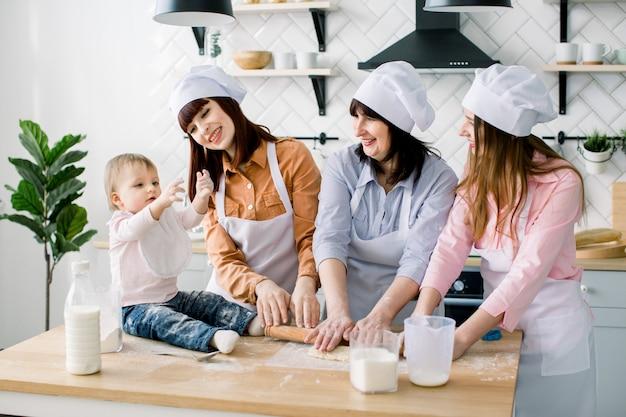 Glimlachende vrouw van middelbare leeftijd in keukenschort deeg uitrollen en twee dochters die haar helpen. weinig babymeisjezitting op de lijst en het hebben van pret. gelukkige vrouwen in witte schorten samen bakken
