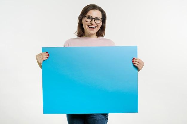 Glimlachende vrouw van middelbare leeftijd met blauw vel plakkaat of poster