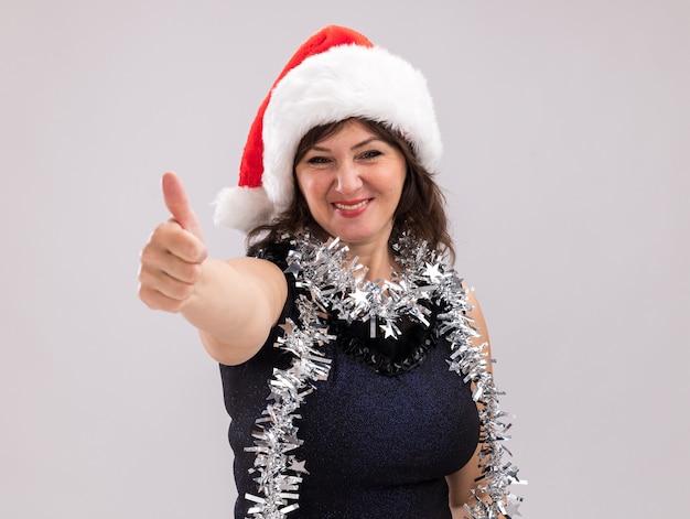 Glimlachende vrouw van middelbare leeftijd met een kerstmuts en een klatergoudslinger om de nek die naar een camera kijkt die duim omhoog laat zien geïsoleerd op een witte achtergrond met kopieerruimte
