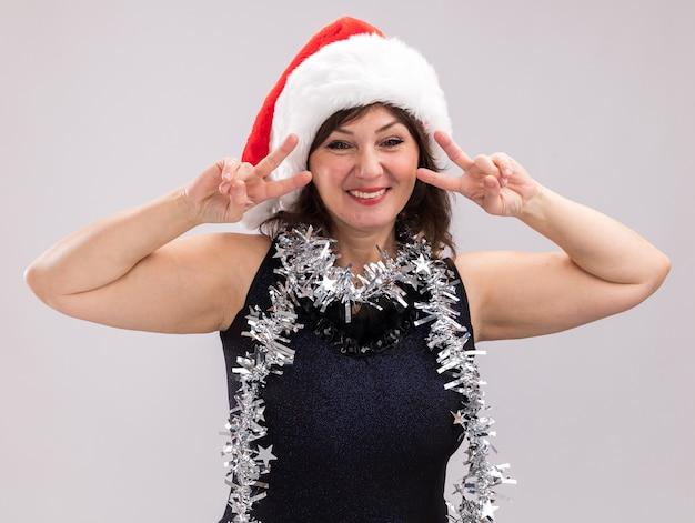 Glimlachende vrouw van middelbare leeftijd met een kerstmuts en een klatergoudslinger om de nek die naar een camera kijkt die vredesteken doet geïsoleerd op witte achtergrond