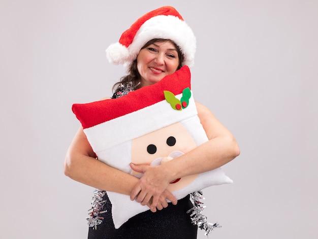 Glimlachende vrouw van middelbare leeftijd met een kerstmuts en een klatergoudslinger om de nek met een kussen van de kerstman en kijken naar camera geïsoleerd op een witte achtergrond met kopieerruimte