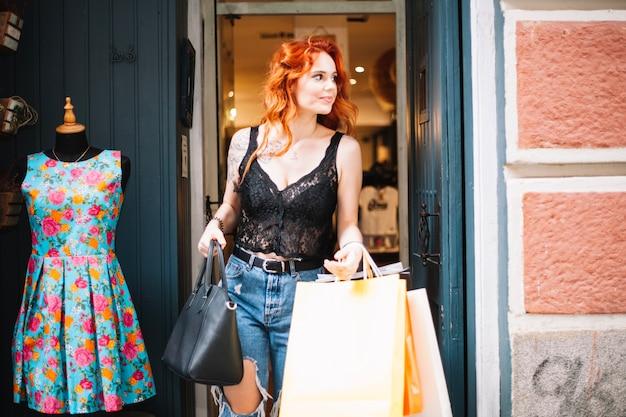 Glimlachende vrouw verlaten winkel