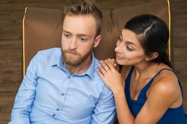 Glimlachende vrouw vraagt peinzende man over iets