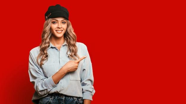 Glimlachende vrouw wijst met één vinger naar lege ruimte, foto op rode achtergrond