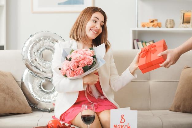 Glimlachende vrouw zittend op de bank op gelukkige vrouwendag geeft cadeau met boeket door iemand in de woonkamer