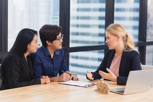 Glimlachende vrouwelijke advocaat of financieel adviseur toont contract- en verzekeringsvormovereenkomst aan multiraciale paarklanten op kantoor, onroerend goed en investeringsaankoopconcept