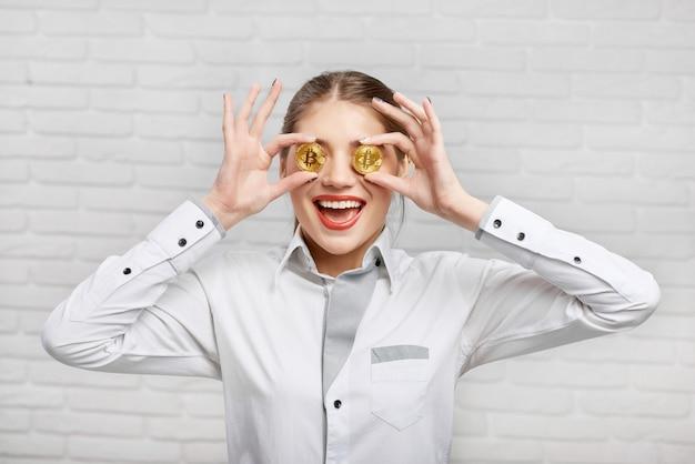 Glimlachende vrouwelijke arbeider in witte slimme blouse die gouden bitcoins voor haar ogen zet