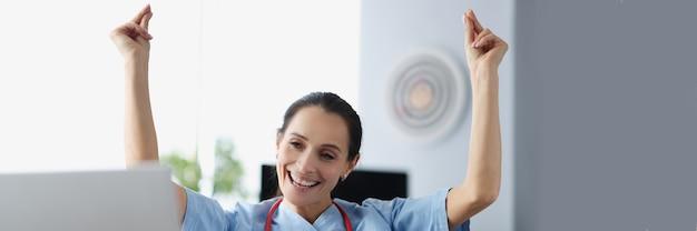 Glimlachende vrouwelijke arts die aan tafel zit en haar handen opsteekt