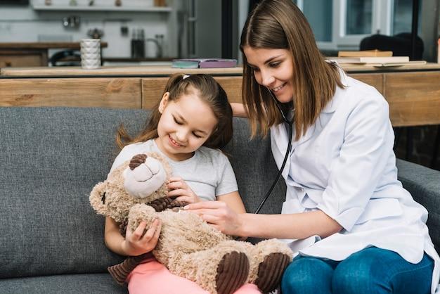 Glimlachende vrouwelijke arts die de teddybeergreep door gelukkig meisje onderzoekt