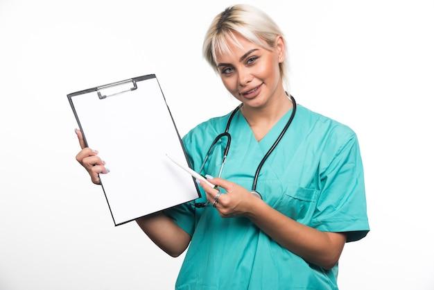 Glimlachende vrouwelijke arts die een klembord met pen op wit oppervlak richt
