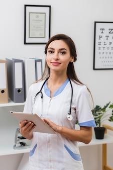 Glimlachende vrouwelijke arts die een omslag houdt