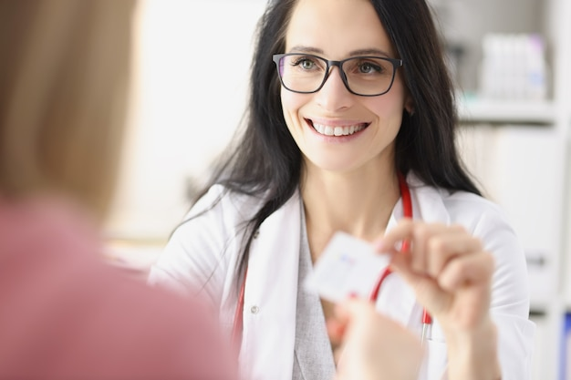 Glimlachende vrouwelijke arts die een visitekaartje geeft aan de patiënt bij de receptie in de persoonlijke arts van de kliniek