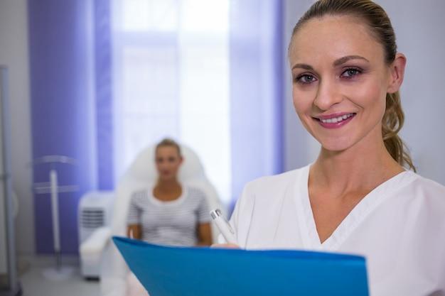 Glimlachende vrouwelijke arts die medische rapporten houdt