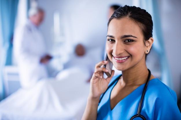 Glimlachende vrouwelijke arts die op een mobiele telefoon spreekt