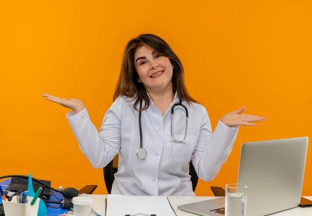 Glimlachende vrouwelijke arts die op middelbare leeftijd medische robe en stethoscoopzitting draagt bij bureau met medische hulpmiddelenklembord en laptop die lege geïsoleerde handen tonen
