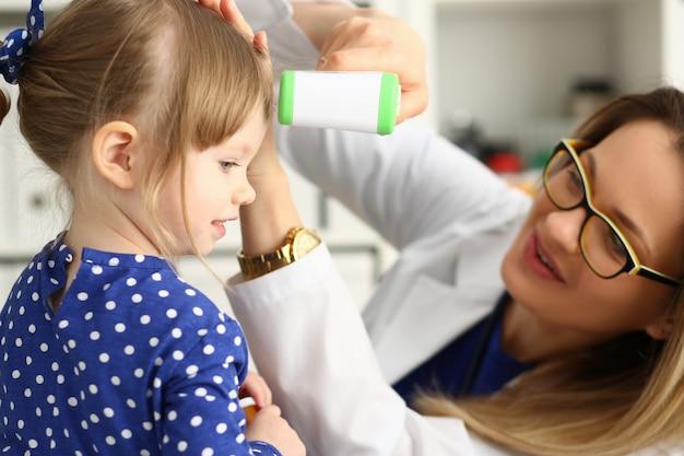 Glimlachende vrouwelijke arts die temperatuur van meisje vergt